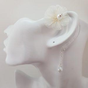 Bijou pour appareil auditif Odiora en forme de petite fleur en tissu mousseline blanc avec une perle au centre de la fleur et au bout de la lacette