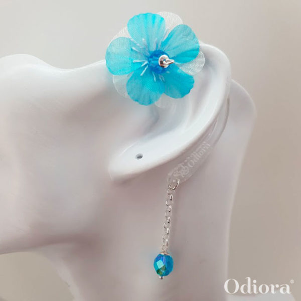 Bijou pour appareil auditif Odiora en forme de petite fleur tissu mousseline bleu turquoise avec une perle au centre de la fleur et au bout de la lacette