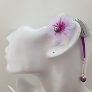 Bijou pour appareil auditif Odiora en forme de petite fleur tissu mousseline rose très pale et violet avec une perle au centre de la fleur et au bout de la lacette