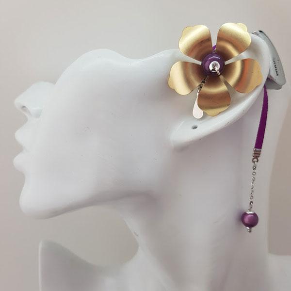 Adénium est un bijou pour appareil auditif en forme de fleur dorée de grande taille ornée de perles magiques et d'une lacette en satin mauve