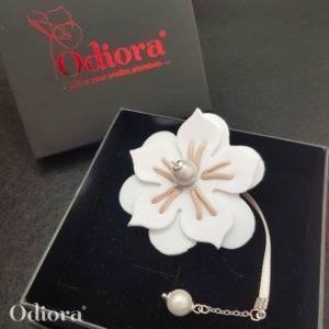 Bijou pour appareil auditif Odiora en forme de fleur d'hibiscus blanche avec une lacette en satin et une perle blanche au bout et au centre de la fleur