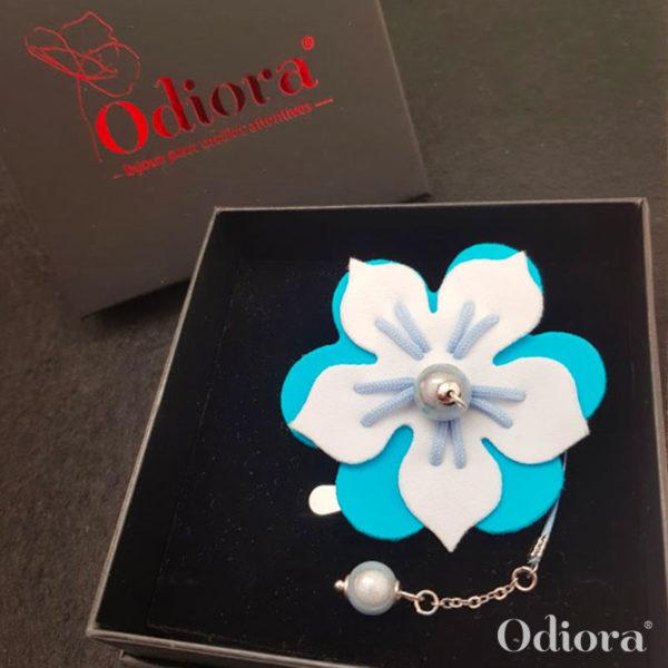 Bijou pour appareil auditif Odiora en forme de fleur d'hibiscus bicolore bleu et blanche avec une lacette en satin et une perle blanche au bout