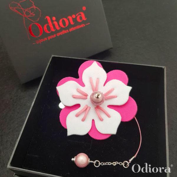Bijou pour appareil auditif Odiora en forme de fleur d'hibiscus bicolore rose et blanc avec une lacette en satin et une perle rose au bout