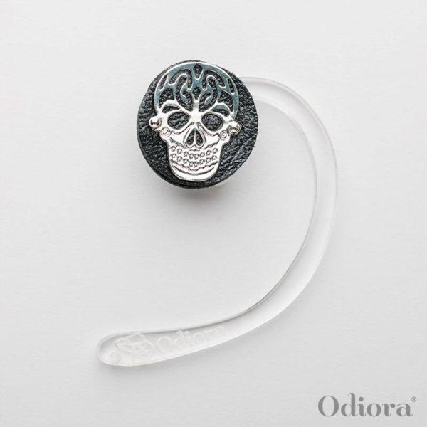 Bijou auditif Odiora composé d'une pièce ronde en cuir noir sur laquelle est apposée une tête de mort en argent. Le bijou est ici sur une accroche solidaire pour personne non-appareillée