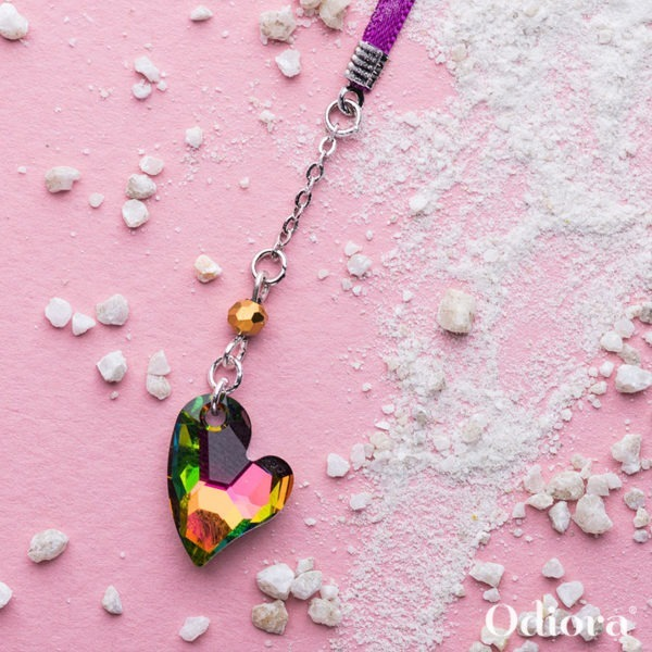Photo de notre bijou pour appareil auditif Love en forme de petit coeur de cristal ici sur fond rose au milieu de grains de sable blanc