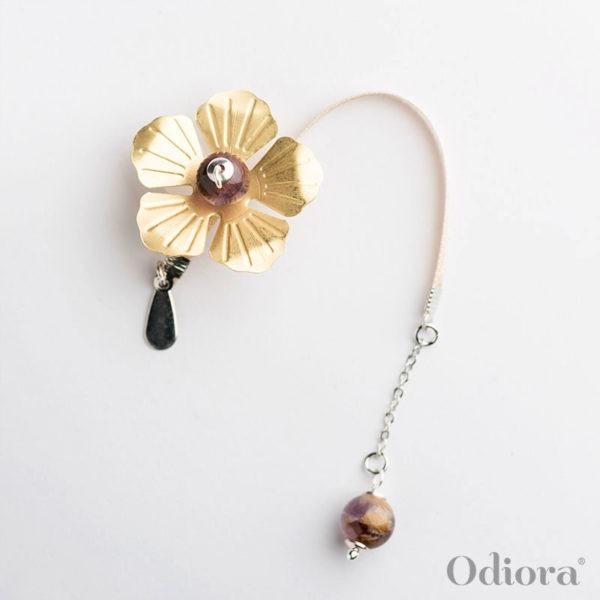 Bijou auditif Odiora en forme de fleur d'Améthyste dorée et mauve avec des perles précieuses et une lacette en satin beige ici sur fond blanc lumineux