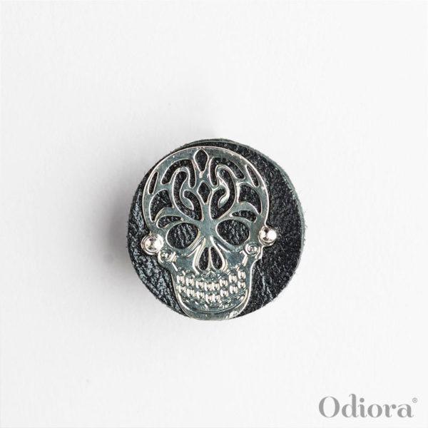 Bijou auditif Odiora composé d'une pièce ronde en cuir noir sur laquelle est apposée une tête de mort en argent ici présenté sur un fond blanc lumineux
