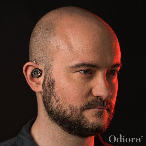 Portrait d'un jeune homme portant un bijou Odiora sur son appareil auditif. Le bijou est composé d'une pièce ronde en cuir noir sur laquelle est apposée une tête de mort en argent