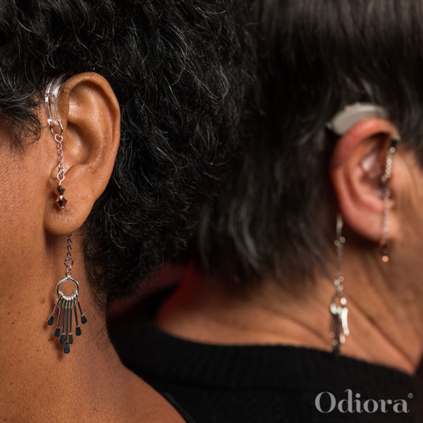 Zoom sur les oreilles de deux femmes, une appareillée avec le bijou auditif Mahana sur son appareil auditif et l'autre avec le même bijou en forme d'attrape rêve sur une accroche solidaire pour personne non-appareillée