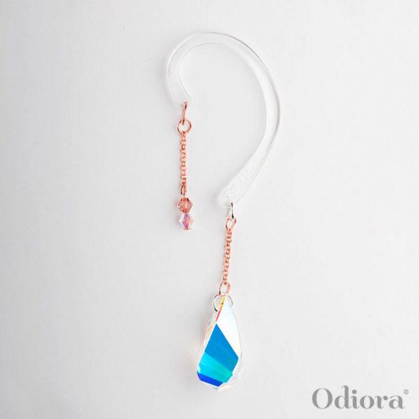 Bijou pour appareil auditif nommé Athéna en forme de grosse goutte de cristal transparent qui change de couleur en fonction de la lumière ici présenté sur son accroche solidaire pour les personnes non-appareillées