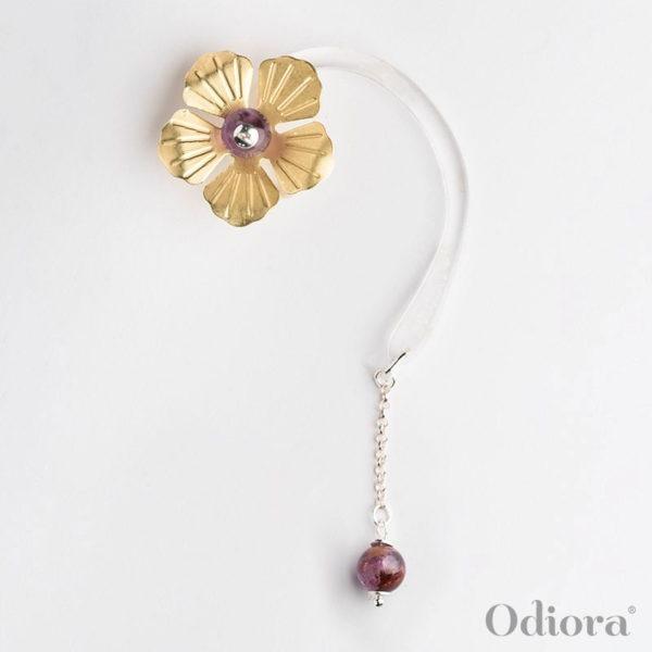 Bijou auditif Odiora avec accroche solidaire pour personne non-appareillée en forme de fleur d'Améthyste dorée et mauve avec des perles précieuses et une lacette en satin beige ici sur fond blanc lumineux