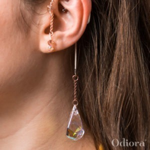 Zoom sur l'oreille d'une jeune femme appareillée portant un bijou auditif Odiora en forme de grosse goutte de cristal transparent