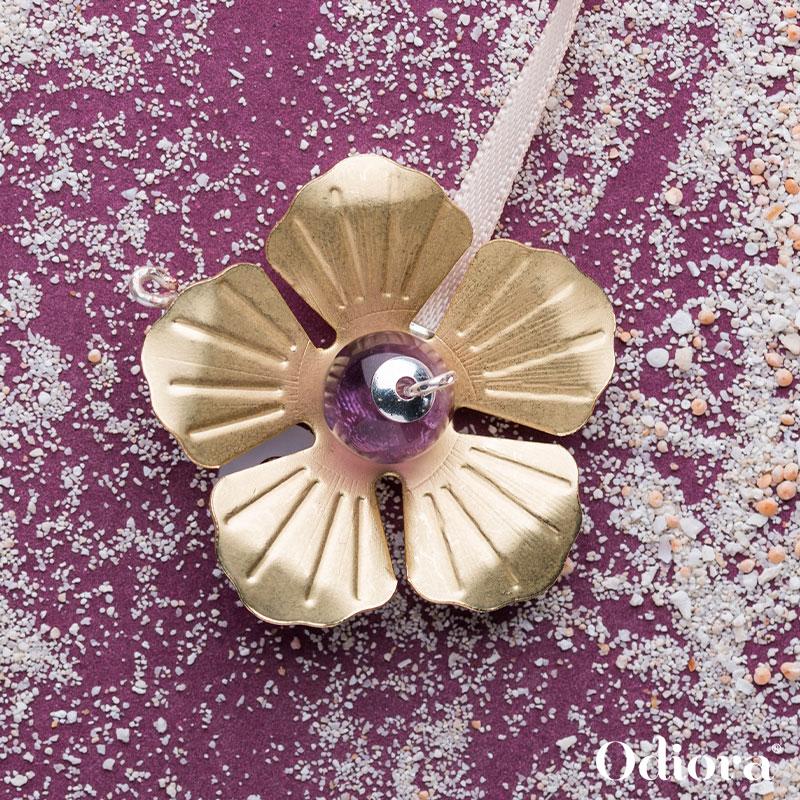 Bijou auditif Odiora en forme de fleur d'Améthyste dorée et mauve avec des perles précieuses ici sur un fond violet avec des grains de sel