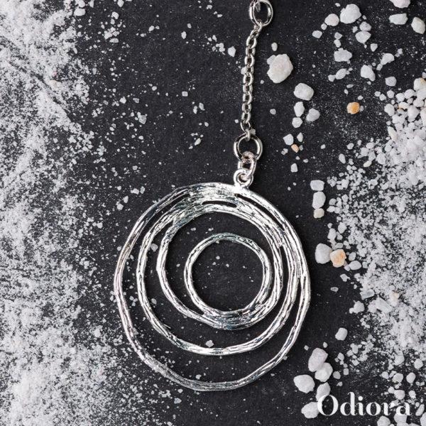 Bijou pour appareil auditif nommé Aquilon pour sa forme de tourbillon en argent ici présenté sur fond noir avec des grains de sable blanc