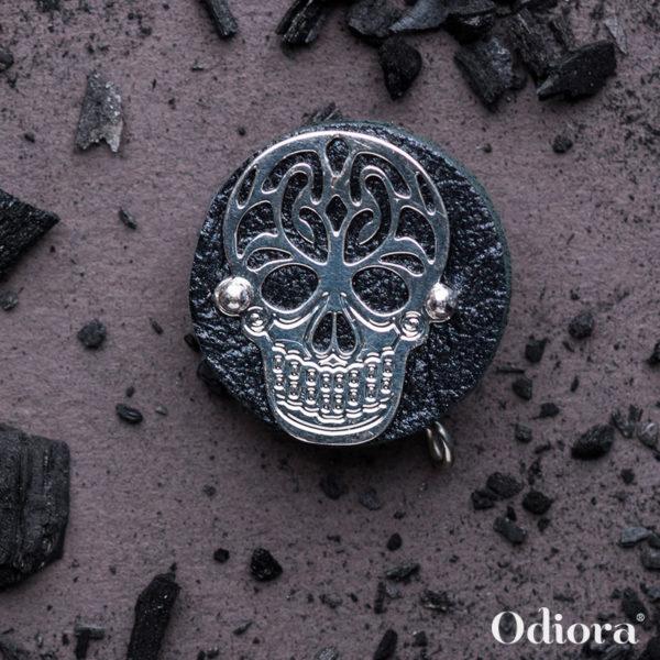 Bijou auditif Odiora composé d'une pièce ronde en cuir noir sur laquelle est apposée une tête de mort en argent ici présenté sur un fond gris avec des bons de charbon en décoration autour