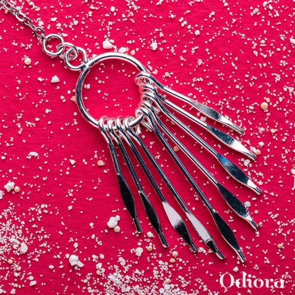 Bijou auditif Mahana en forme d'attrape rêves en argent sur fond rose avec grains de sel