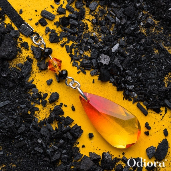 Zoom sur le bijou auditif Phoenix ici sur fond jaune entouré de cendres pour faire ressortir les couleurs rouges orangées de sa goutte en cristal