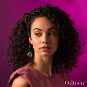 Portrait d'une jeune femme métisse portant un bijou pour appareil auditif Odiora en forme de tourbillon en argent
