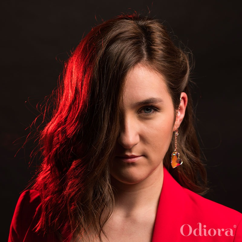 Portrait d'une jeune femme portant un bijou auditif Odiora en forme de gros coeur en cristal transparent