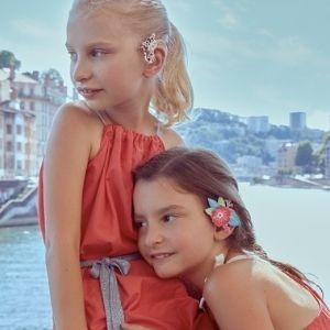 Portrait de deux jeunes femmes portant Phoenix notre bijoux pour appareil auditif en forme de goutte de cristal aux reflets rouge, orange et jaune