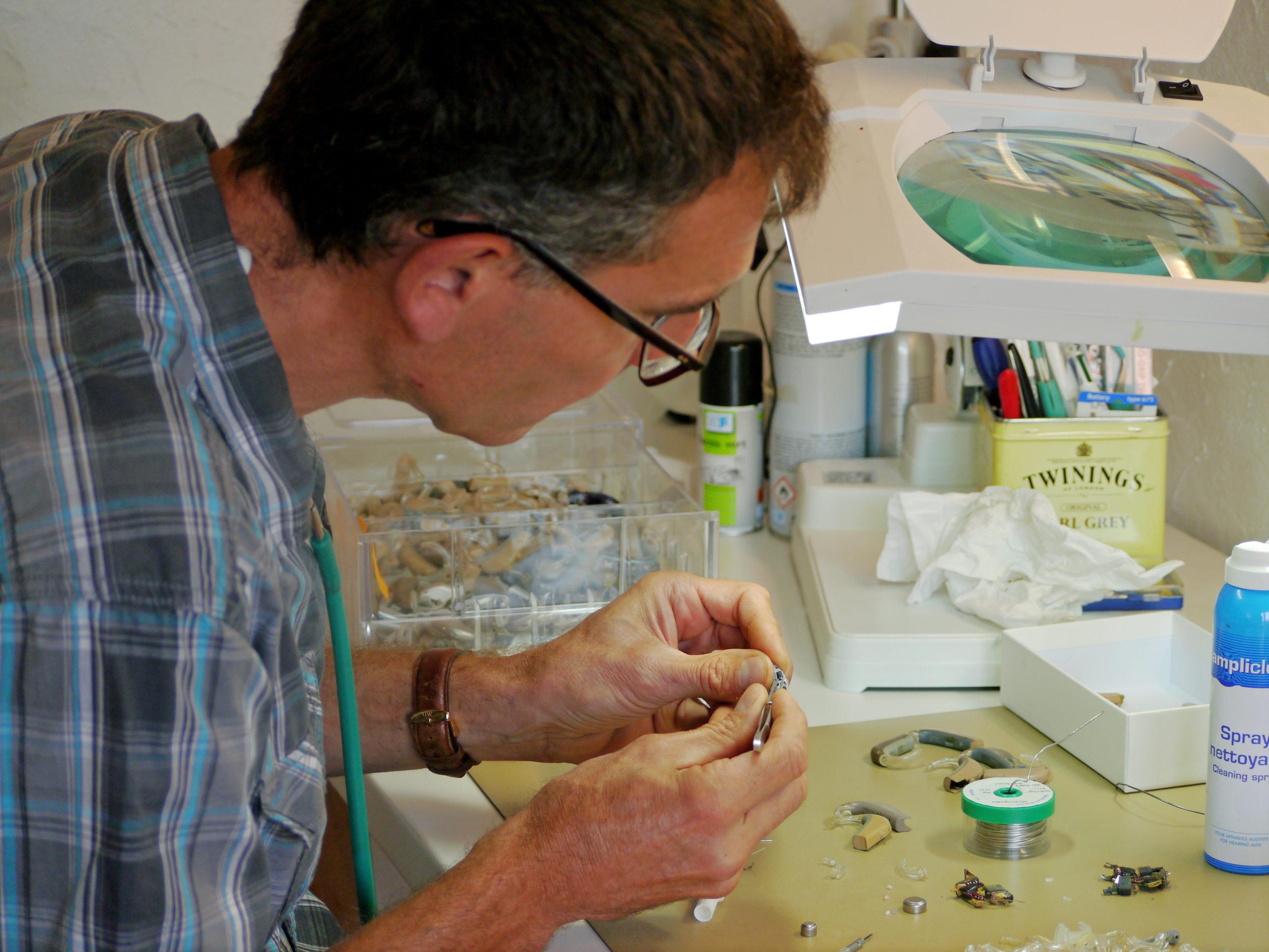 Photo d'un audioprothésiste en train de réparer des appareils auditifs recyclés par l'association Audition Solidarité